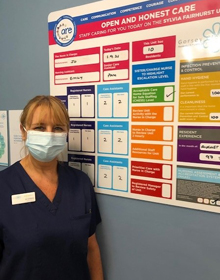 Nurse in front of safety notice board
